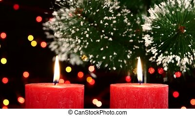 Top of two red candles with christmas decorations and tree on black, bokeh, light, garland