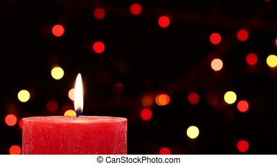 Top of two red candles with christmas decorations on black, bokeh, light, garland