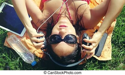 Top of view of beautiful young woman in sunglasses lying on the grass, listening to music and singing song. 3840x2160, 4k