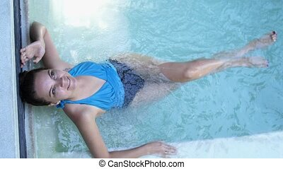 Beautiful woman relaxes in a hydromassage jacuzzi, in swimming pool. Concept: spa procedures, body massages, spa cream, relax, spa water treatments