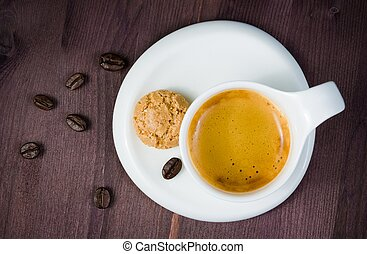 top of view of cup of espresso coffee and biscuit near coffee beans