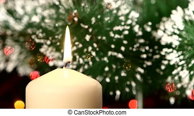 Top of white candle with christmas decorations and tree on black, bokeh, light, garland