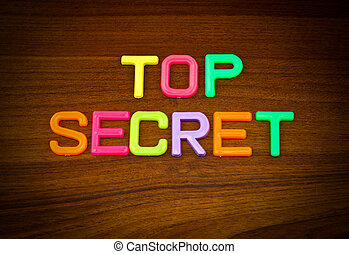 Top secret in colorful toy letters on wood background