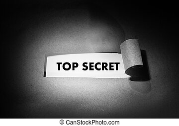 """Top secret"" phrase behind torn brown paper. Black and white photo, spot light"