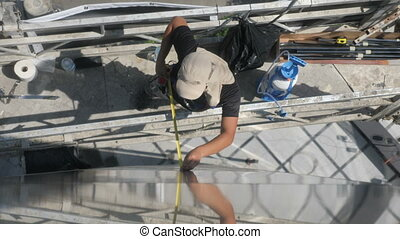 Top Shot of construction worker performing measurements shot...