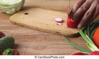 Top shot of man chef cutting radish on chopping board - Top...