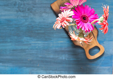 Top shot of pink flowers on a blue background and on a small table.