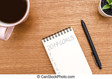 Top view 2019 goals list with notebook, cup of coffee on wooden