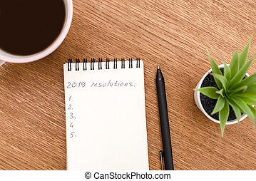 Top view 2019 resolutions list with notebook, cup of coffee on wooden desk