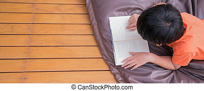 Top view A boy reading a book at home.  Learning at home concept