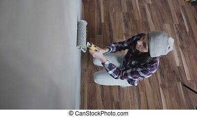 Top view - a young beautiful girl in gray hat draws the walls with a roller in gray paint. A woman makes repairs in her new apartment