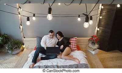 Top view - a young man with a pregnant wife sits on the bed and using their laptop at home. Conception of pregnancy