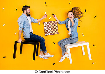 Top view above high angle flat lay flatlay lie view concept of her she his he nice cheerful cheery crazy friends playing chess having fun isolated on bright vivid shine vibrant yellow color background