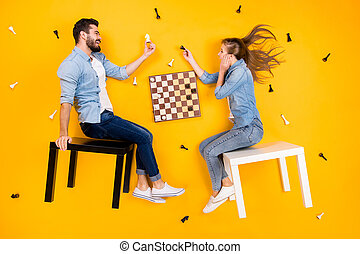 Top view above high angle flat lay flatlay lie view concept of her she his he nice cheerful partners sitting on stool playing chess isolated on bright vivid shine vibrant yellow color background