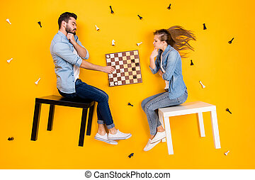Top view above high angle flat lay flatlay lie view concept of her she his he nice focused clever spouses sitting on stool playing chess isolated on bright vivid shine vibrant yellow color background
