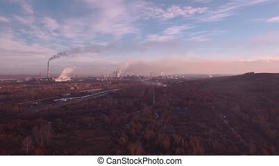 Top view, AERIAL: autumn landscape and industrial plant. Air pollution from industrial plants. Pipes throwing smoke in the sky. 4K