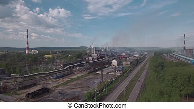 Top view, AERIAL: highway and industrial plant. Air pollution from industrial plants. Pipes throwing smoke in the sky. 4K