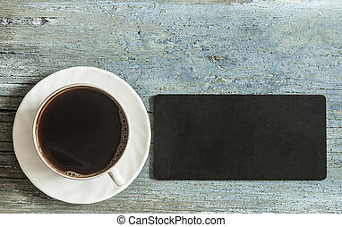 small empty blackboard for your text, a cup of hot coffee on wooden background