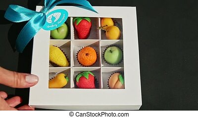 top view at hand takes away and puts back gift box with assorted fruits shaped candies