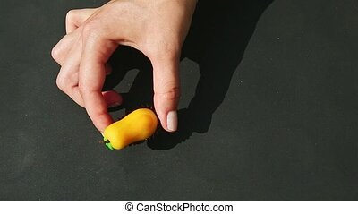 top view at woman hand shows and takes away yellow pear shaped marzipan candy