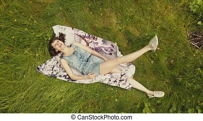 Top view beautiful young woman relaxing on grass in summer day