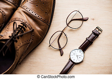 top view brown shoes, glasses and watch on wooden surface