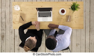 Business, technology and office concept - serious businessman and businesswoman with laptop making video call
