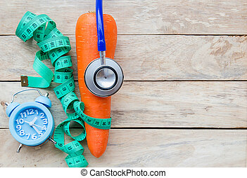 Top view carrot with blue stethoscope,measuring tape on wood table background.