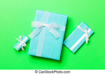 Top view Christmas present box with white bow on green background