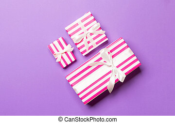 Top view Christmas present box with white bow on purple background