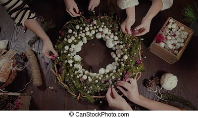 top view Christmas wreath on craft background, pretty women...