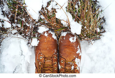Top view close-up hiking leather boots on covered snow forest trail