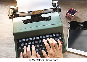 Top view close up of lady hands using vintage green typewriter placed on wooden desk, love word written on scrabble block