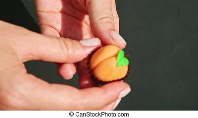top view closeup confectioner hands put pear shaped marzipan candy on brown stand