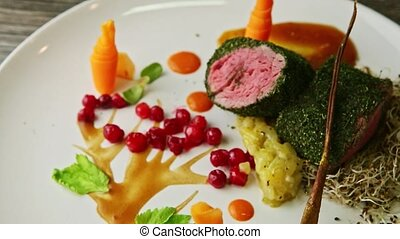 top view closeup exquisite decorated trendy restaurant dish of meat roasted in dill served with wheat sprouts, assorted sauces, and viburnum berries on white plate
