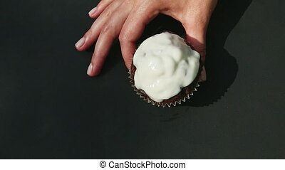 top view closeup female hand puts tasty homemade chocolate cupcake decorated with white glaze on black table surface