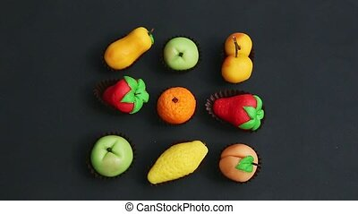 top view closeup hand takes away fruit shaped marzipan candy from assortment