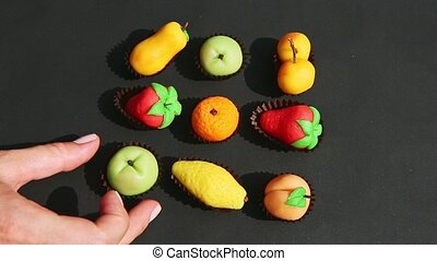 top view closeup hand takes away fruits shaped marzipan candies from assortment