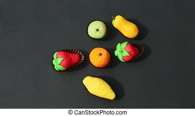 top view closeup hand takes away fruits shaped marzipan candy from assortment