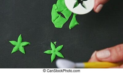 top view closeup woman hands make star shaped leaves from bright green marzipan mass on black table surface