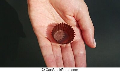 top view closeup human hands put strawberry shaped candy into brown stand