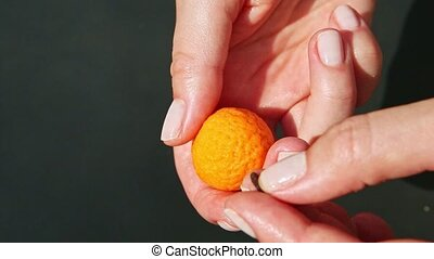 top view closeup on female hands insert dry clove into small orange marzipan ball