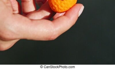 top view closeup on woman hands show small orange shaped marzipan candy