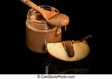 top view closeup peanut butter in glass jar with slice of apple