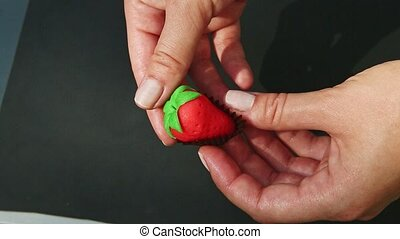 top view closeup woman hands show red strawberry shaped marzipan candy