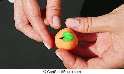 top view closeup woman hands show small peach shaped marzipan candy