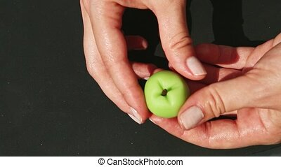 top view closeup woman shows in hands small green apple shaped marzipan candy