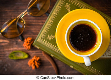 top view, coffee and book with autumn leaves on wood background - seasonal relax concept