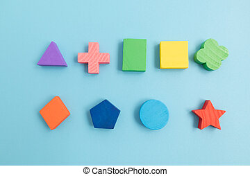 Top view Colorful Wooden building blocks with different shapes for developing and entertainment of Children on blue background.