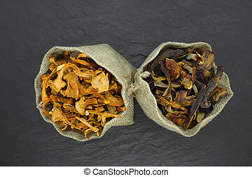 Top view composition of dry boletus and chanterelles mushrooms placed in canvas on black stone background surface with copy space